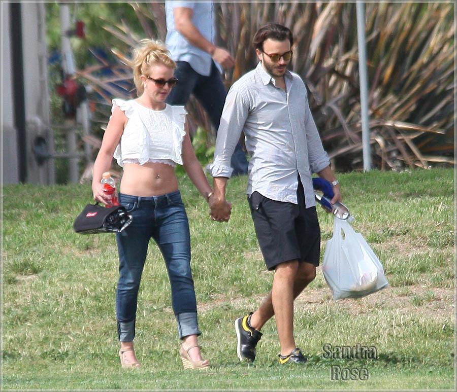Britney Spears shows off her abs in a white crop top and blue jeans