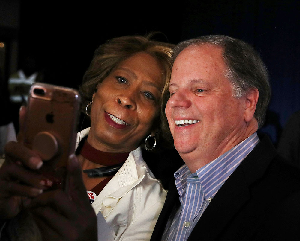 Doug Jones takes a selfie with a supporter during a get out the vote campaign rally