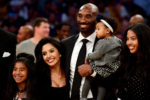 Kobe Bryant poses with his family at halftime after both his #8 and #24 Los Angeles Lakers jerseys are retired
