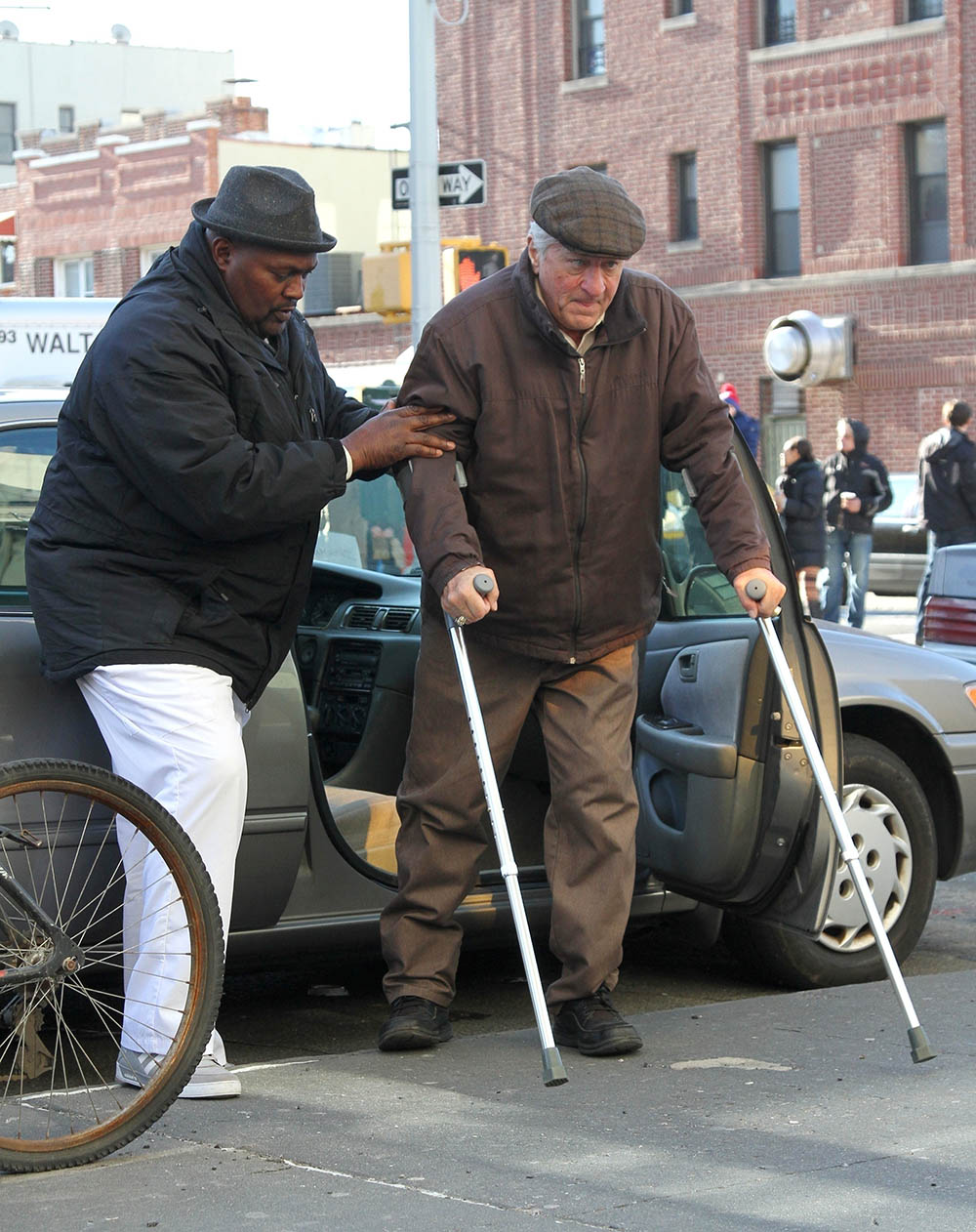 An older looking Robert De Niro is assisted out of his car while filming The Irishman