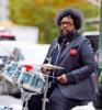 Questlove plays drums on the sidewalk in Tribeca