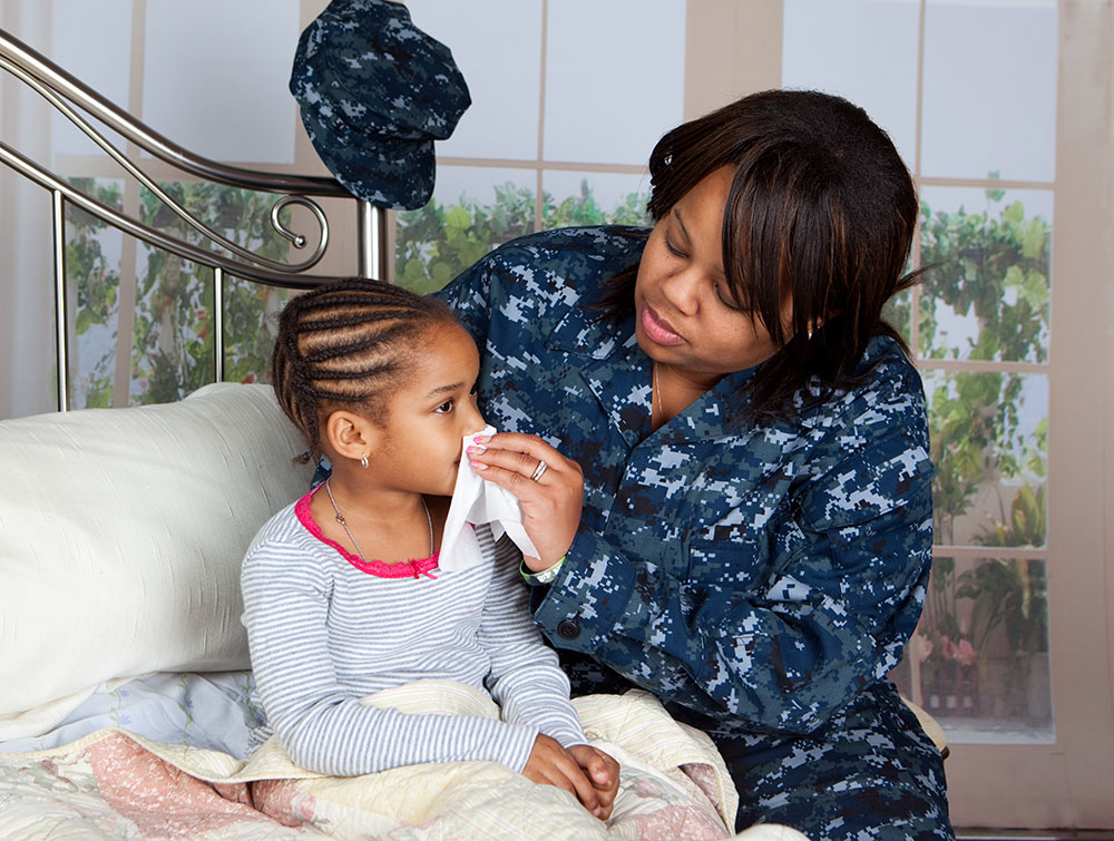 Military mom wiping her daughter's runny nose