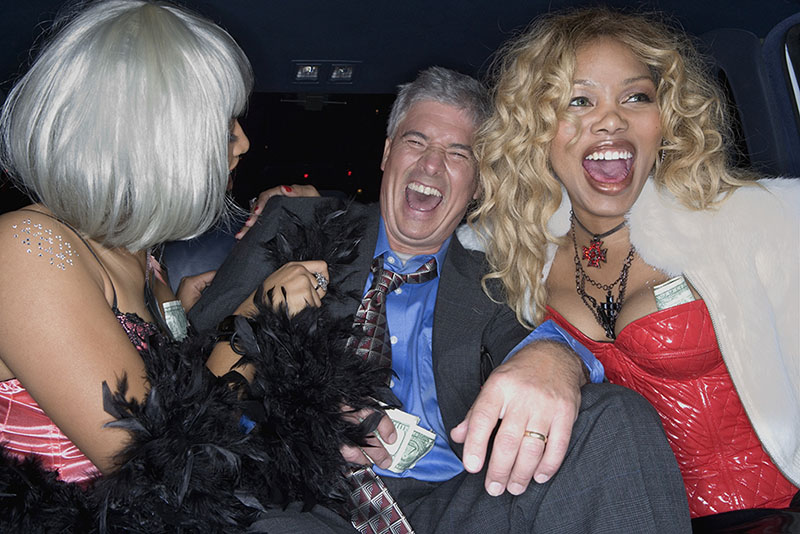 Stock photo - Middle-aged man laughing in limousine with prostitutes