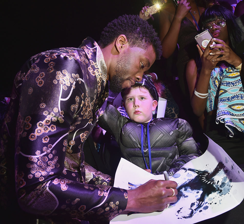 Chadwick Boseman signs autograph for young fan at the LA Premiere of Black Panther